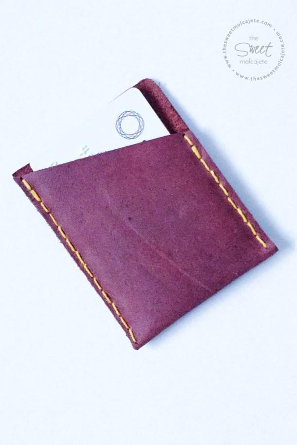 Vista de arriba a una cartera de piel color marron con costuras amarillas y con un par de tarjetas dentro