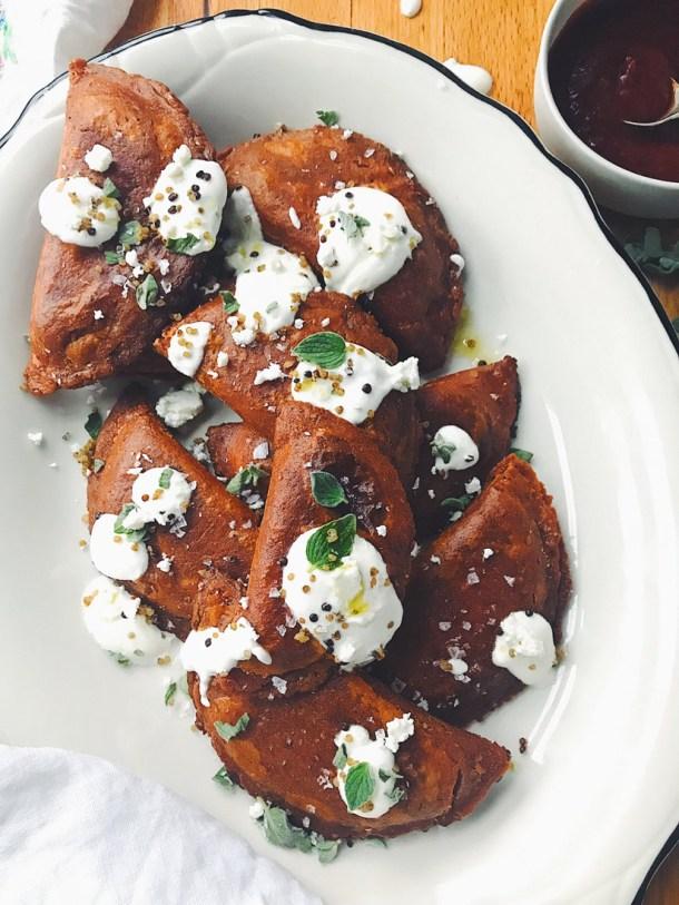 Plato largo con varias Enchiladas Potosinas adornadas con crema cilantro y chile de arbol. Recetas para el Dia del Padre