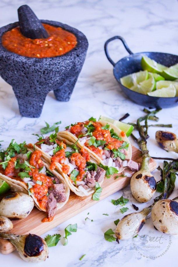 Tres tacos de lengua acompañados de cilantro, cebolla y salsa roja sobre una tablita y con cebollitas asadas a un lado para celebrar el Dia del Padre