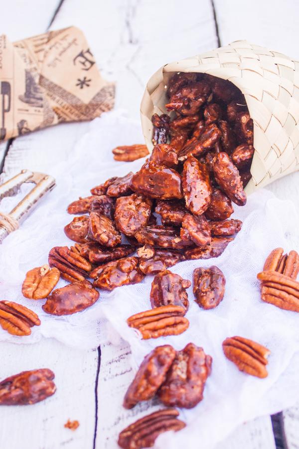 Cajita de petate llena de nueces garapiñada volteada sobre la mesa, se ven las nueces saliendo de la cajita