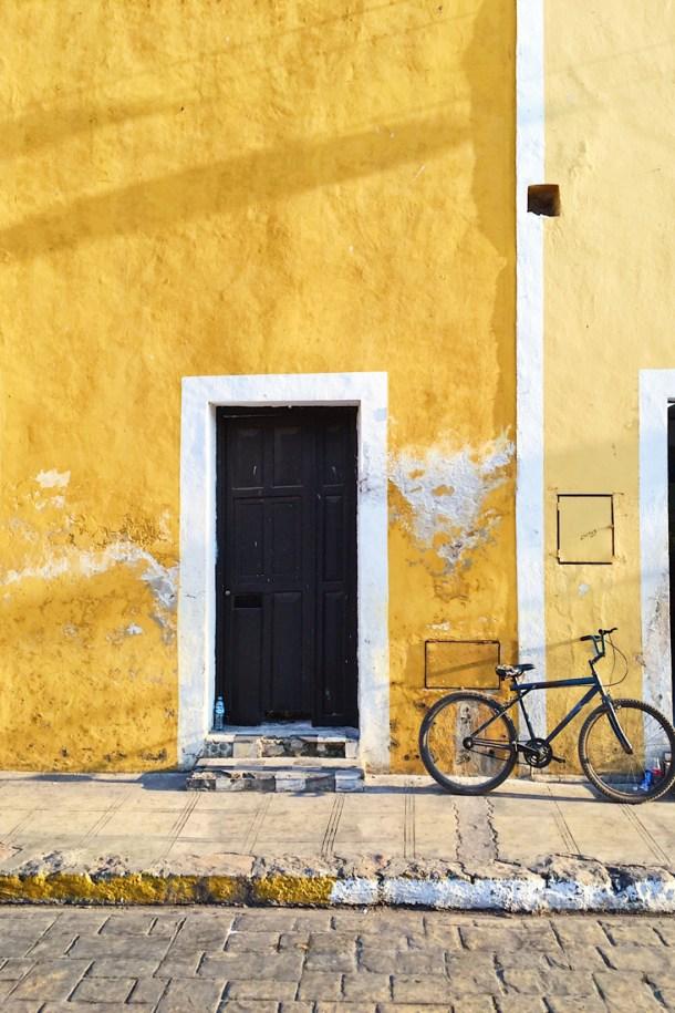 Bicicleta recargada en las paredes amarillas de Izamal, Yucatán