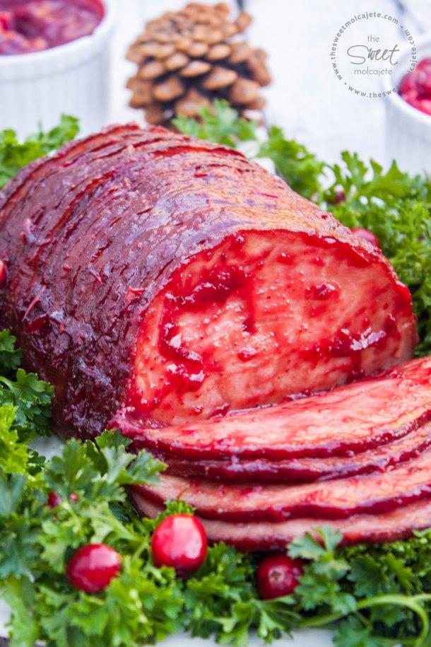 Acercamiento de un Jamón Glaseado con Salsa de Arándanos y Chipotle que descansa sobre una cama de perejil con arándanos frescos alrededor. El jamón está rebanado y las primeras rebanadas del jamón descansan sobre el plato.