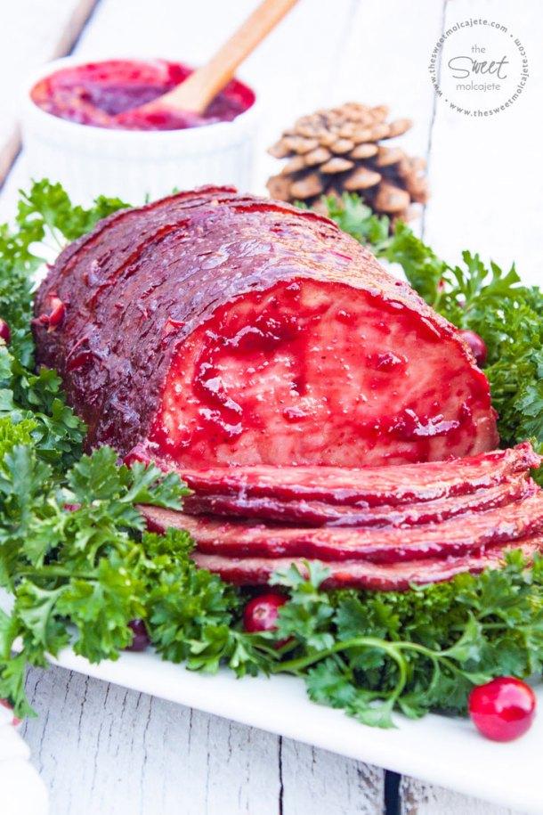 Jamón Glaseado con Salsa de Arándanos y Chipotle que descansa sobre una cama de perejil con arándanos frescos alrededor. El jamón está rebanado y las primeras rebanadas del jamón descansan sobre el plato.