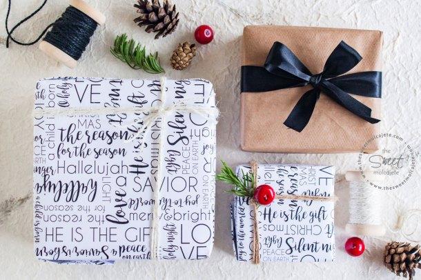 Vista aérea de 3 regalos navideños acomodados en forma paralela uno a otro junto a otros objetos de navidad como piñas de pino, ramitas de pino y cordones rústicos. Dos de los regalos están envueltos con una linda envoltura de regalos para Navidad con un bello diseño con tipografía en blanco y negro.
