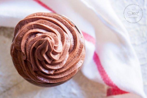 Betún de Chocolate en forma de espiral como si fuera helado visto de arriba. Hay un trapito de tela blanco a un lado del frasco que contiene el betún.