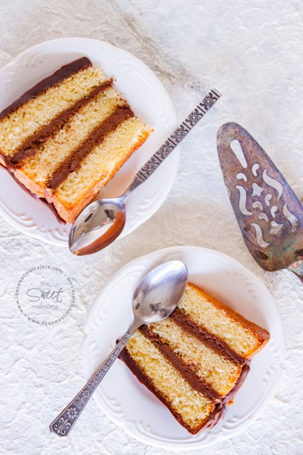 Vista de arriba de dos rebanadas de pastel de mantequilla con relleno de buttercream de chocolate y con cubierta de ganache de chocolate. Las rebanadas de pastel descansan sobre dos platos blancos pequeños y cada uno tiene una cuchara a un lado.