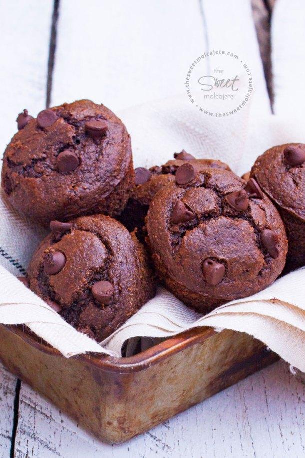 Acercamiento a varios muffins de chocolate sin gluten acomodados en un molde para pan de metal cubierto con tela de lino