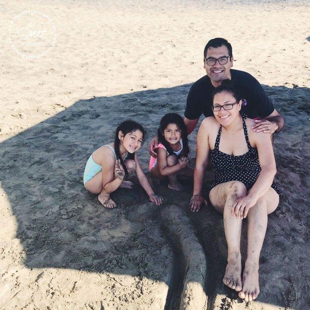 Fotografía de una familia jugando en la arena de la playa de Manzanillo - Vida Slow