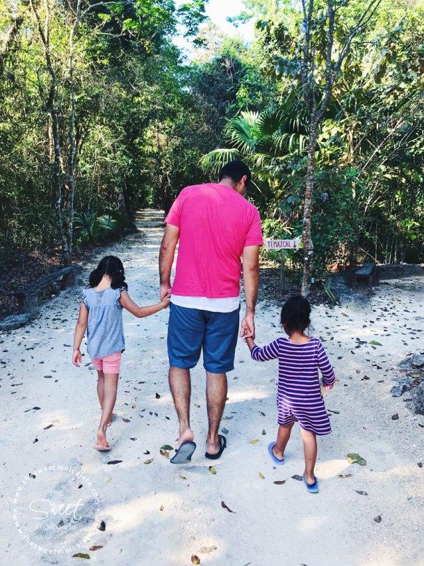 Papá llevando de la mano a sus dos hijas en medio de un camino empedrado en la selva - Vida Slow