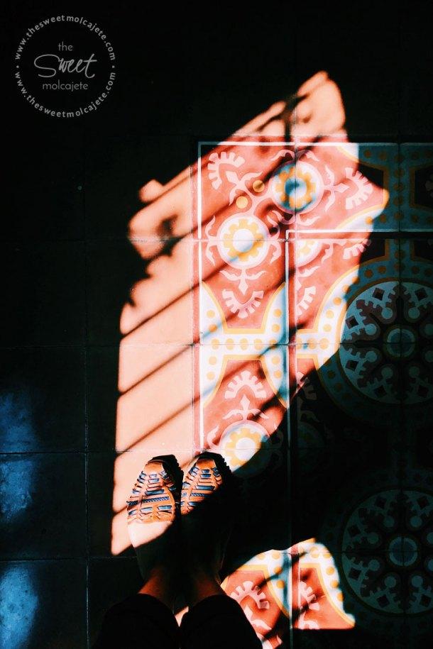 Fotografía de los rayos del sol que entran por una ventana con barrotes reflejados en un piso con mozaicos color marrón de estilo colonial - Vida Slow