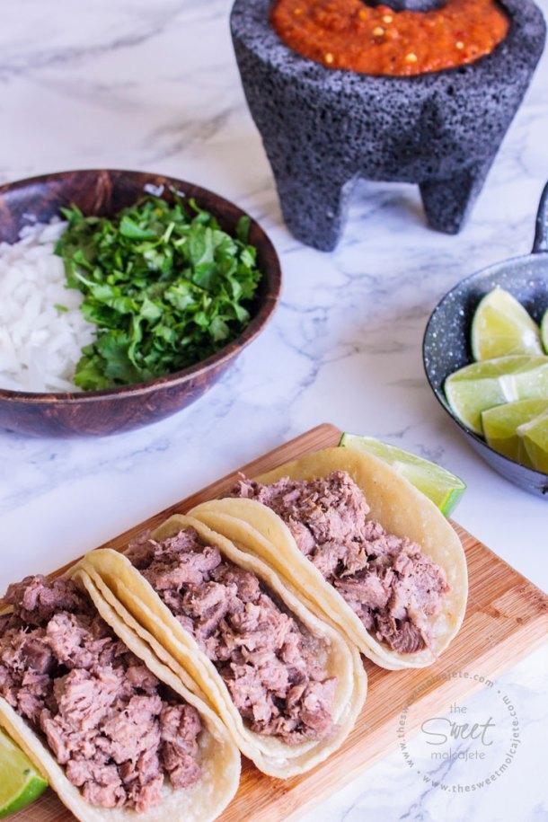 Tres tacos de lengua de res servidos en una tablita de madera. En la mesa se ven limones, un molcajete con salsa roja y un plato con cilantro y cebolla.
