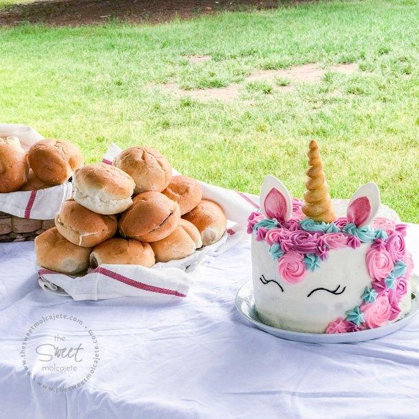 Mesa del parque cubierta con un mantel de tela, con un pastel de unicornio, y sandwichitos de ensalada de pollo dentro de canastas a un lado. Fiesta Zero Waste o con menos basura