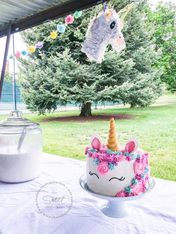 Fiesta Zero Waste o con menos basura, en el parque. En la mesa, cubierta con mantel de tela, se ve un pastel de unicornio, agua de horchata en un recipiente grande de cristal, una piñata hecha en casa y flores de papel como adornos