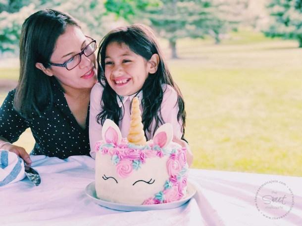 Mamá e hija en una fiesta zero waste, pastel unicornio sobre la mesa del parque, la mesa está cubierta con un mantel de tela