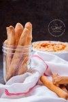 Foto de Palitos de Pan crujientes caseros dentro de un mason jar, una telita blanca alrededor del frasco y un par de palitos sobre ella. Al fondo se ve un recipiente con Hummus casero.