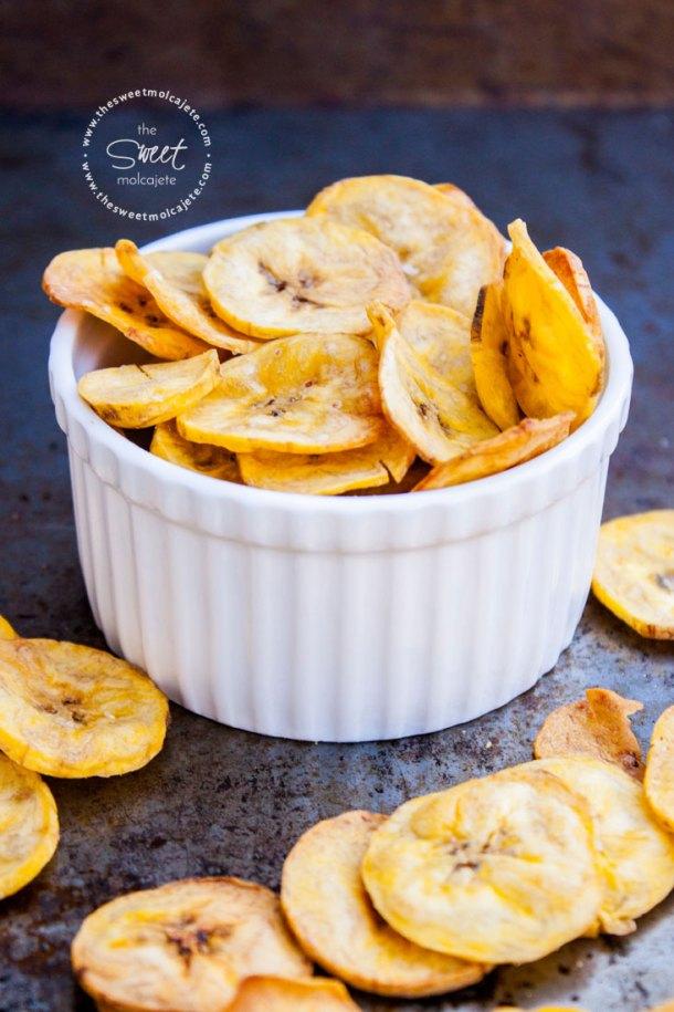 Imagen de un recipiente de cerámica blanco lleno de platanitos deshidratados saludables, hay más platanitos regados por la mesa - 15 ideas de snacks saludables