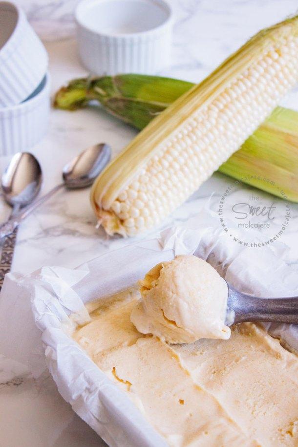 Foto de helado de elote recién salido del congelador y con una cuchara para helado haciendo una bola, se ven elotes frescos al fondo y unas cucharas a lado del molde de helado