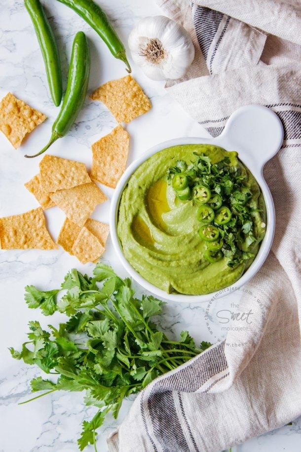 Toma aérea del Hummus Verde de Cilantro con Chile. Se ve también en la mesa totopos, chiles, ajos y cilantro