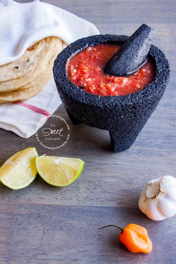 Salsa Roja con Habanero en un molcajete de piedra y una servilleta de tela con tortillas de harina