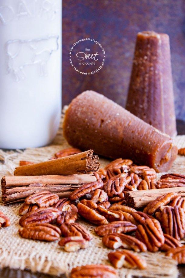 Ingredientes para hacer Atole de Nuez sobre una base rústica: Nueces pecanas, piloncillo, canela y leche.