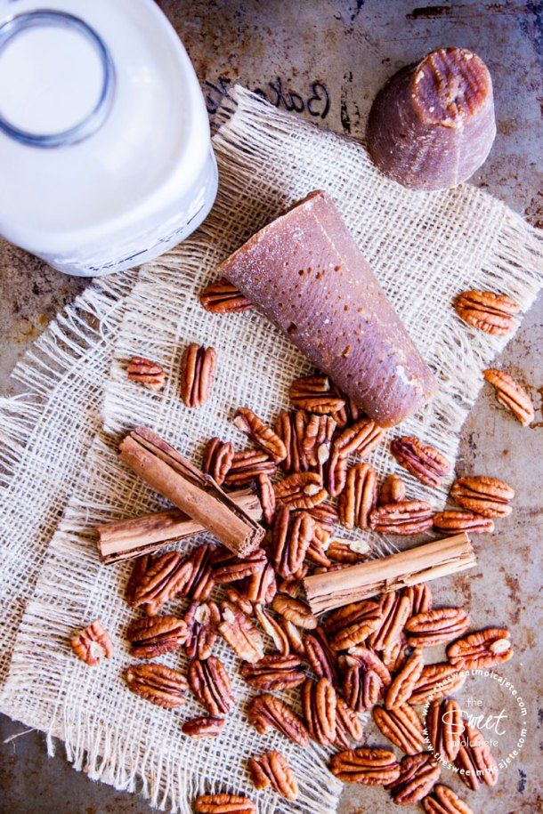 Ingredientes para hacer atole de nuez: leche, canela, piloncillo y nuez pecana sobre una base rústica