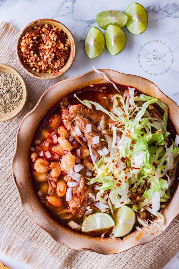 Vista de arriba de un plato de pozole rojo con carne de cerdo, lechuga y otros condimentos