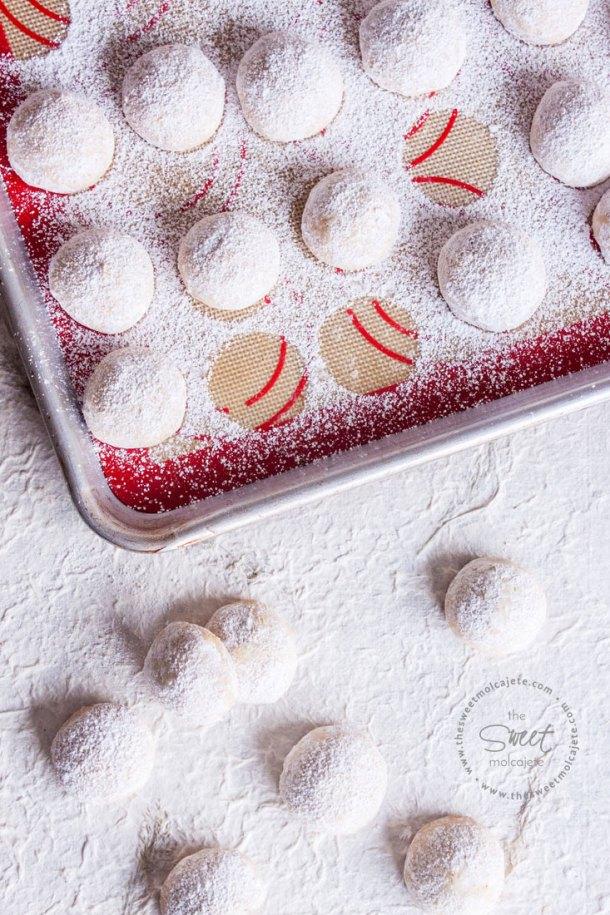 Bolitas de Nuez o Besos de Nuez recién espolvoreados con azúcar glass sobre la charola de galletas