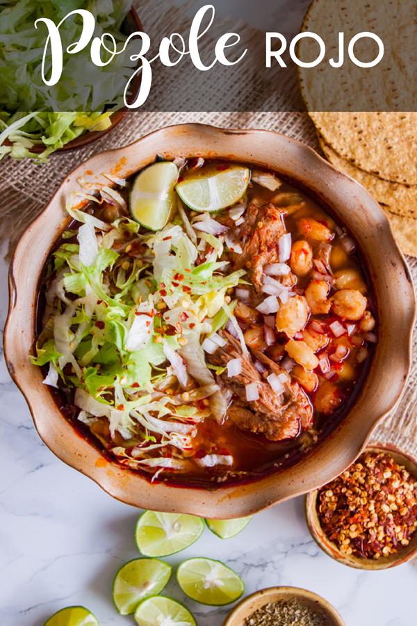 Vista aérea de un plato de pozole rojo con carne de cerdo con lechuga y otros condimentos con texto que dice pozole rojo