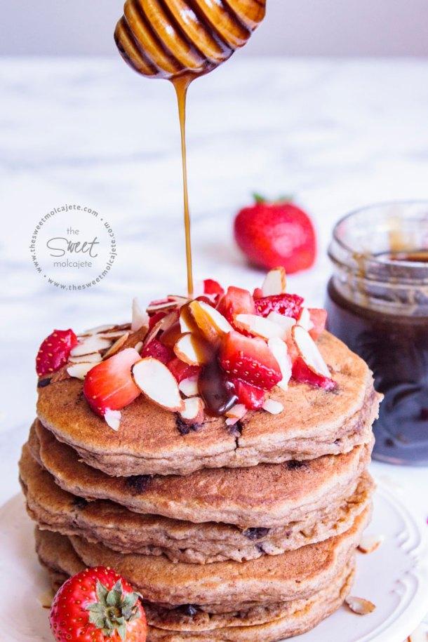 Acercamiento a un plato de Hotcakes Integrales con Avena con una palita de miel echándoles miel encima