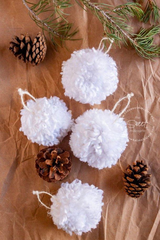 Vista cenital a una mesa con 4 adornos de navidad con estambre blanco que se ven como esferas para árbol de navidad