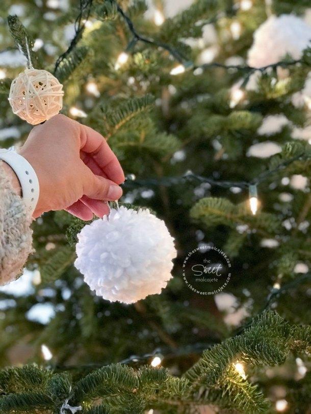 Mano colgando un adorno de navidad con estambre blanco en un árbol de navidad