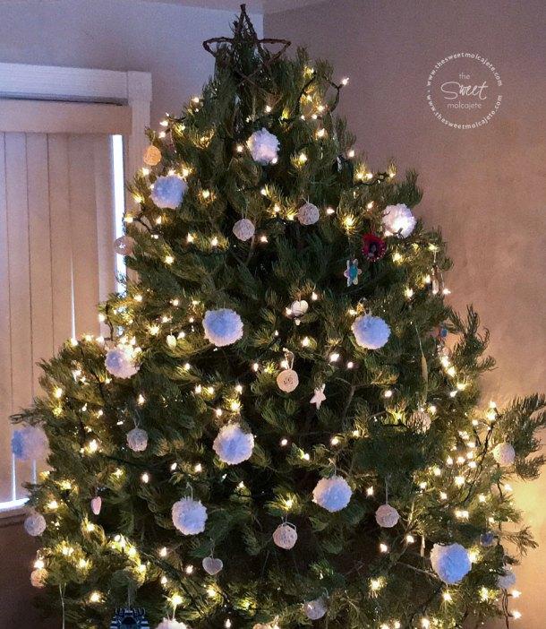 Árbol de Navidad frondoso con adornos de navidad con estambre