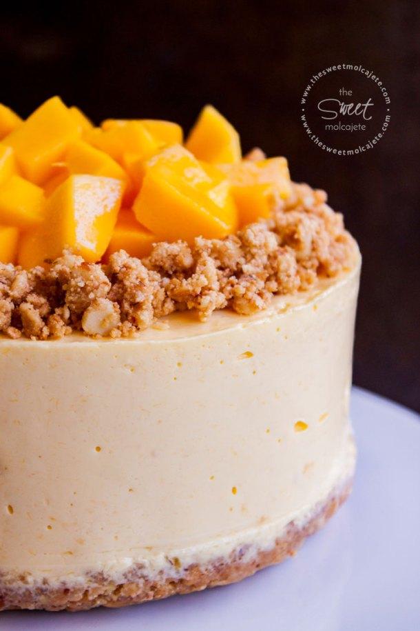 Acercamiento a un cheesecake de mango sin horno que está decorado con galleta con almendras y cubitos de mangos frescos en la superficie
