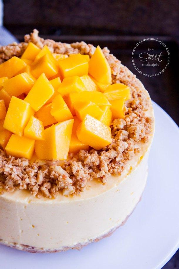 Cheesecake de Mango sin Horno decorado con galleta con almendra y cubitos de mango fresco en el centro. El cheesecake está sobre un plato blanco