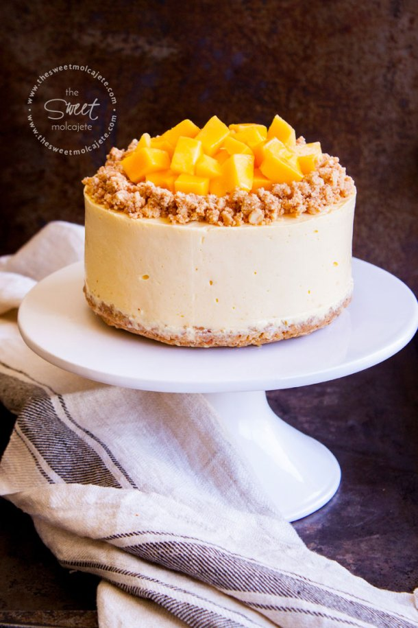 Toma completa a un Cheesecake de mango sin horno que está sobre un cake stand blanco