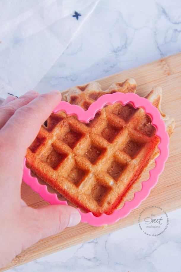 Mano cortando un waffle con un molde en forma de corazon
