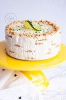 pastel carlota de limon adornado con galletas en trozos y una rebanada de limón