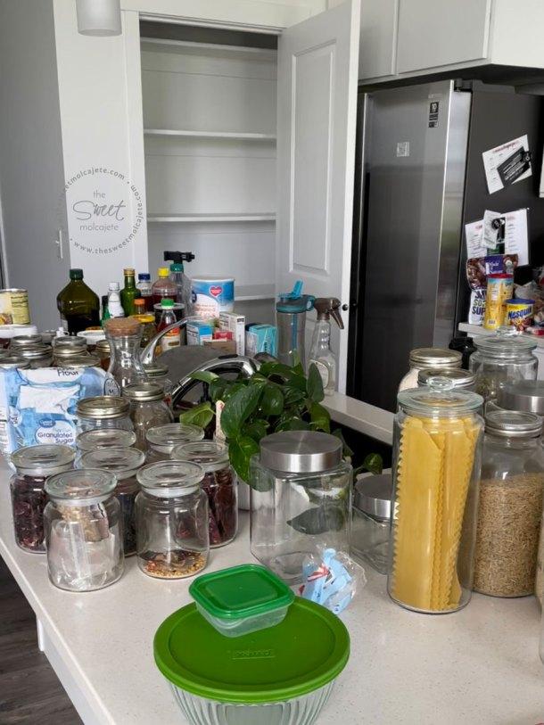 todos los contenidos de la despensa en la barra de cocina, al fondo se ve la despensa completamente vacía