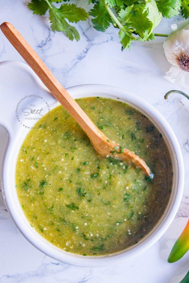 vista de arriba a un plato con salsa verde picante con una cucharita de madera
