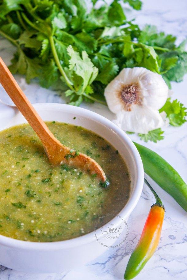 recipiente con salsa verde picante y una cucharita de madera, hay un manojo de cilantro, una cabeza de ajo y chiles serranos sobre la mesa