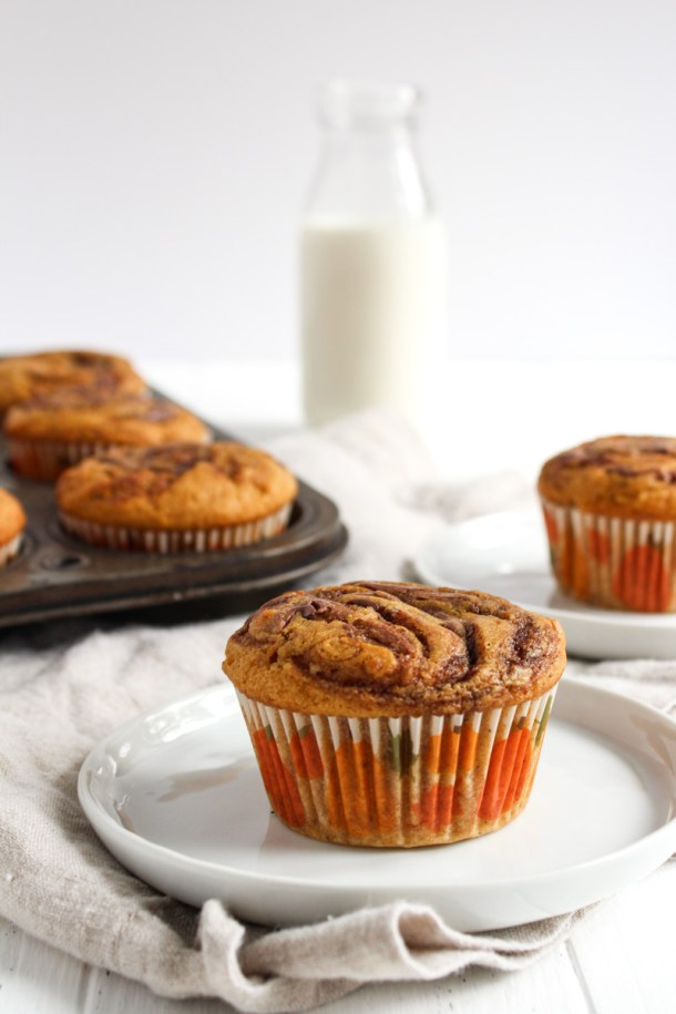 Two pumpkin Nutella muffins on plates with more still in the muffin tin in the background.