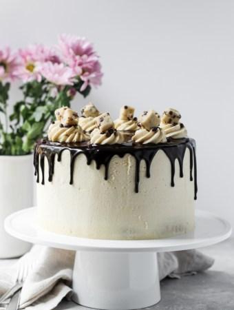 Round layered cookie dough cake with buttercream and chocolate ganache drip