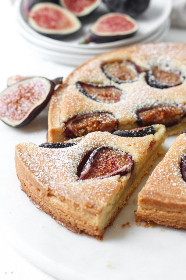 Side angle close up of fresh fig tart with almond cream filling and slice cut.