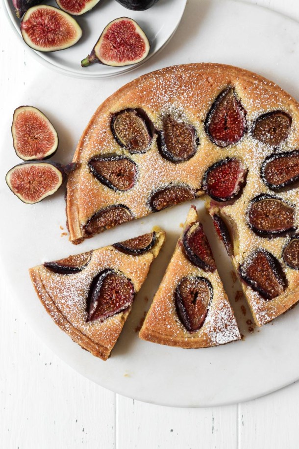 Looking down on fresh fig tart with an almond cream filling with two slice cut.