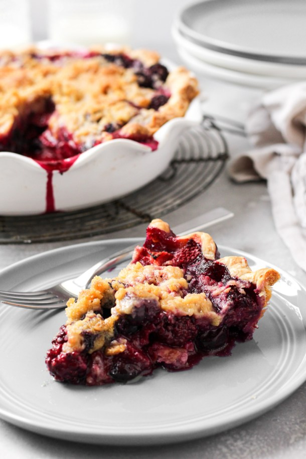 Slice of mixed berry pie with crumb topping.