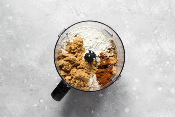 Food processor bowl with crumble topping ingredients.