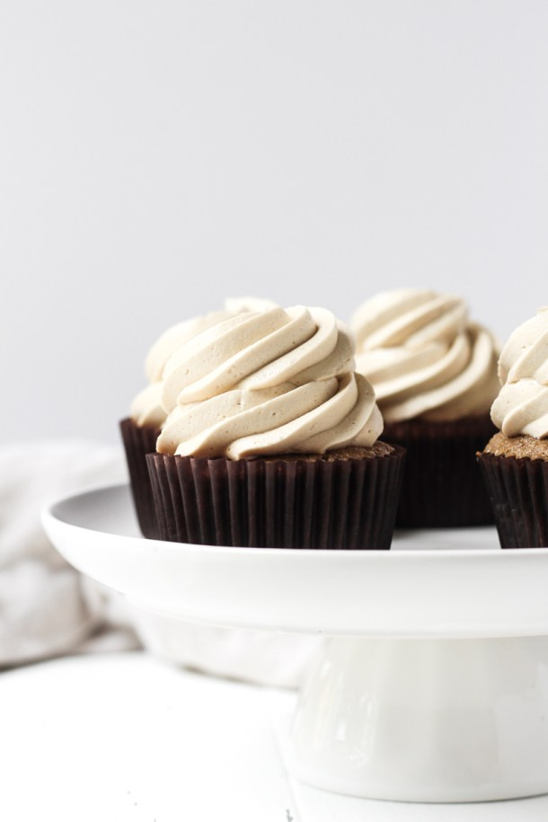 Coffee cupcakes with coffee buttercream on a cake stand.