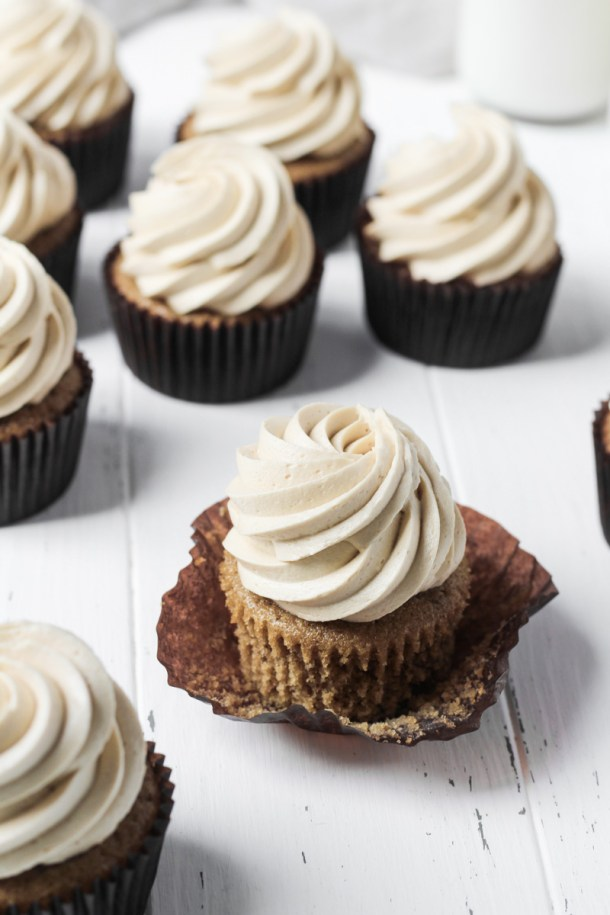 Several coffee cupcakes with coffee buttercream on a white wood board for display with one cupcake with the wrapper loosened.