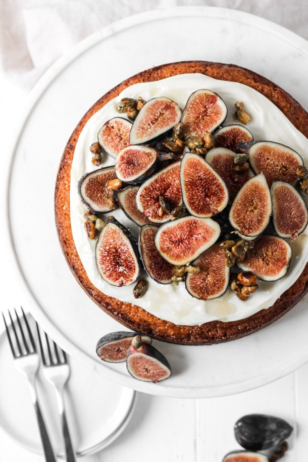 Overhead shot of fig cake with fresh seasonal figs, cream cheese frosting, honey and nuts on a cake stand.
