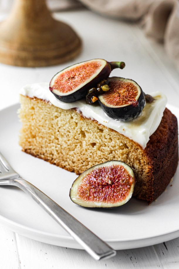 Slice of fig cake with cream cheese frosting, fresh figs, honey and candied nuts on a white plate with a fork.